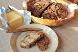 Leipäkorissa on ruisleipä, josta on leikattu viipaleita. Leipäkorin vierellä avoinainen voipaketti. Lautasella kaksi ruisleipäviipaletta, joista toinen on voideltu voilla.