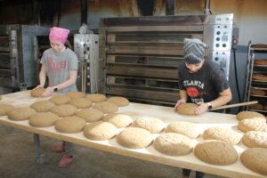 Pitkän leipiä täynnä olevan pöydän takana kaksi nuorta naista silottelee leivinlapioiden päälle nostettujen ruisleipien pintaa. Taustalla paistouuni.