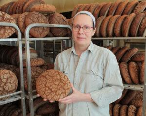 Tiina Muhonen esittelee Muhosen leipomon juuri paistettua luomuruisleipää.