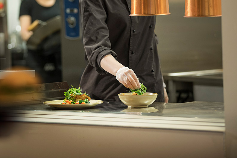 Kuvassa keittiötyöntekijä viimeistelee kahta lautasilla olevaa ruoka-annosta. Ruoka-alan kiinnostavuuden ja alan osaamisen lisääminen ovat keskeisiä tulevaisuuden kehittämiskohteita. Kuva: Manu Eloaho/Darcmedia