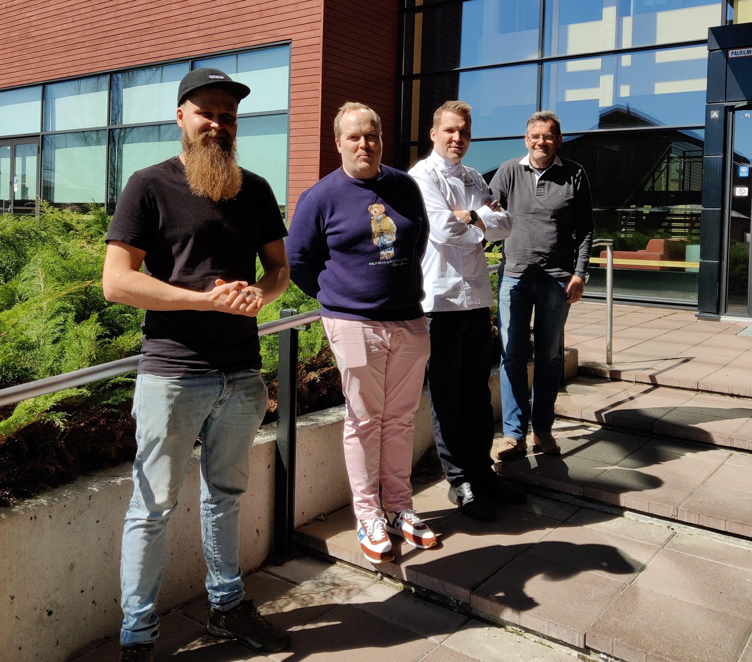 Neljä miestä seisoo ulkona vierekkäin.