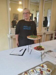 Nainen seisoo pöydän takana, päällä Maistuvaa muikusta -logolla varustettu esiliina. Naisen edessä pöydällä esillä pitsa ja ruokaannos, jossa on pyöryköitä ja perunamuusia.