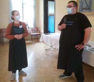 Nainen ja mies seisovat vierekkäin, Molemmilla on Maistuvaa muikusta -logolla varustetut esiliinat päällä.